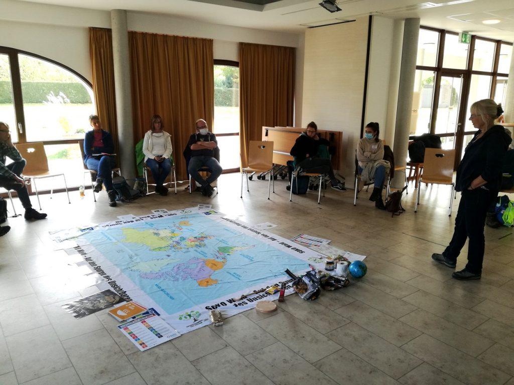 Stuhlkreis mit Teilnehmern, in der Mitte liegt eine Weltkarte