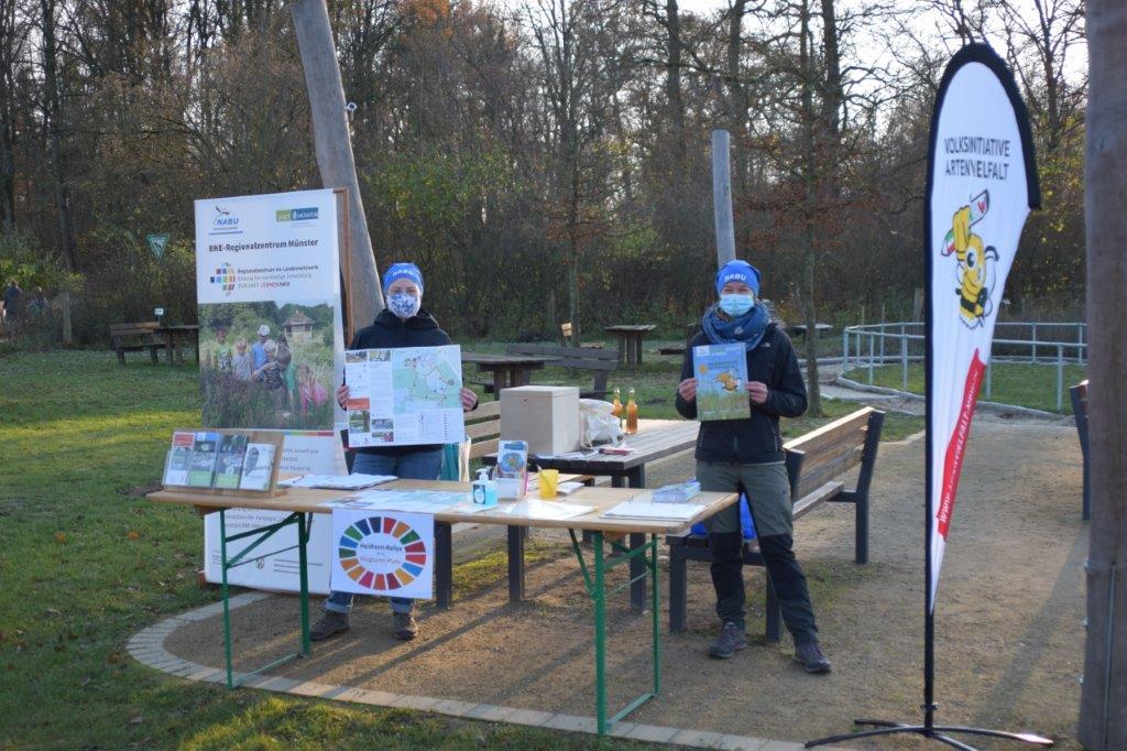 Zwei Mitarbeiterinnen des NABU-Münsterland stehen hinter dem Rallye-Stand und halten Karten hoch