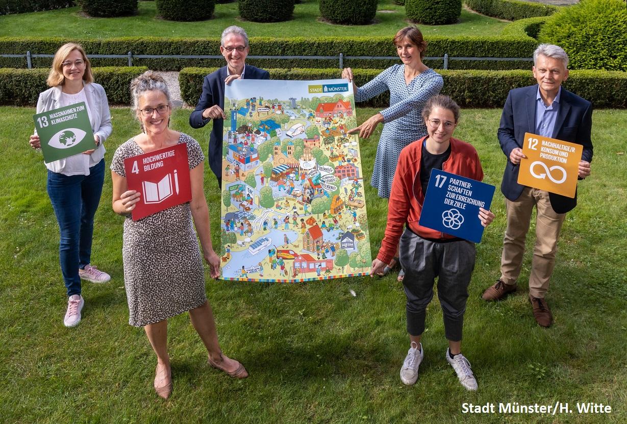 Sechs Menschen präsentieren ein Wimmelbild-Plakat und ausgedruckte Globale Nachhaltigkeitsziele
